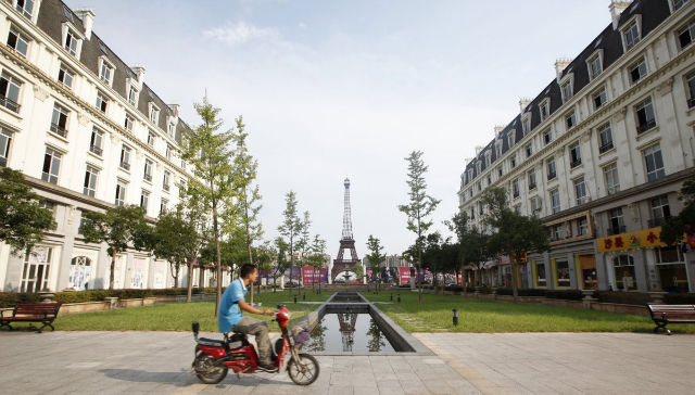 A man rides a motorcycle past a replica of the Eiffel Tower