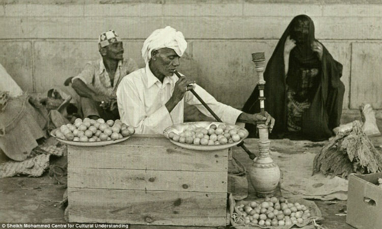 A man smelling lemons and herbs, while smoking a shisha