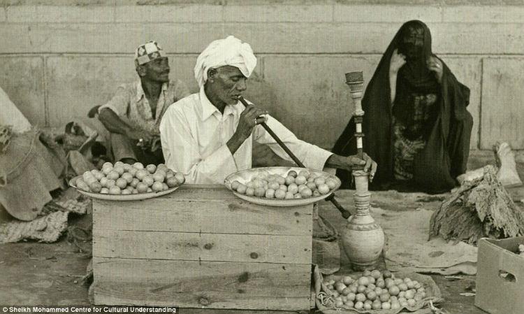 A man smelling lemons and herbs, while smoking a shisha