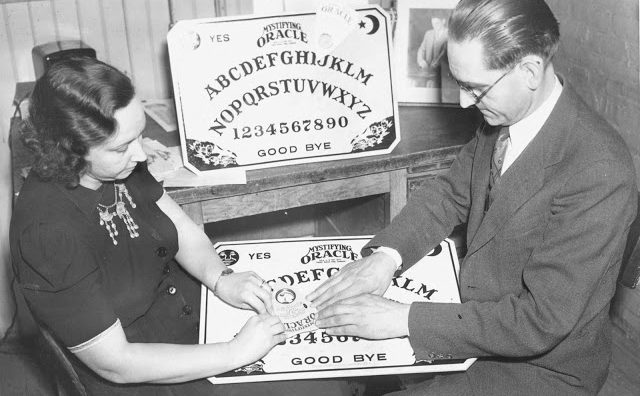 Man and woman playing Ouija board