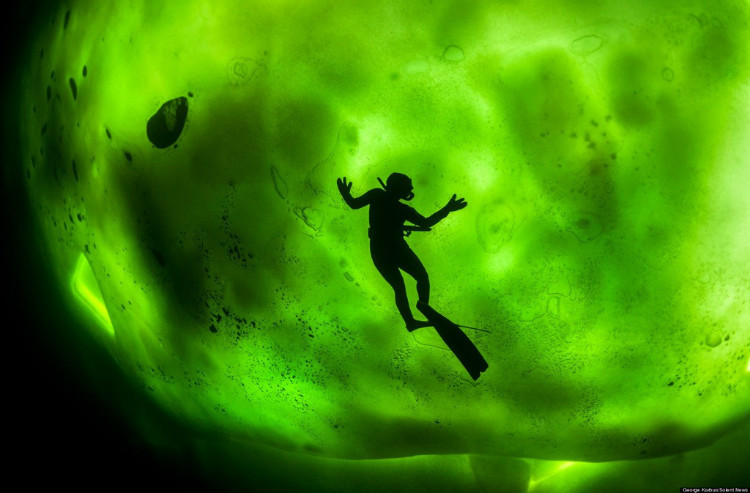Diver beneath thick ice, Northern Lights