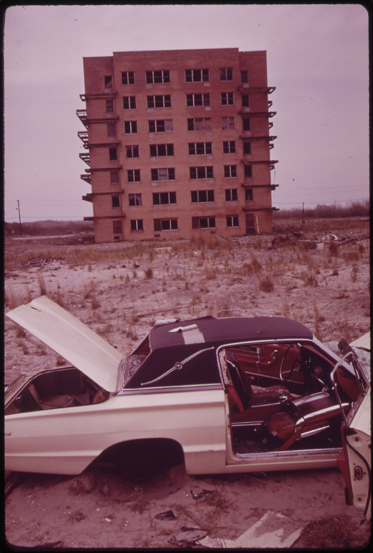Abandoned Car and Unfinished Apartment House