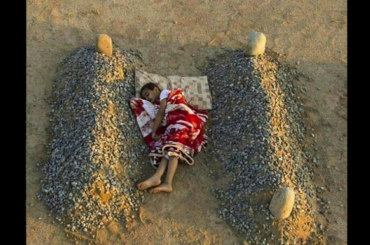 Syrian Boy Sleeping Between Parents' Graves
