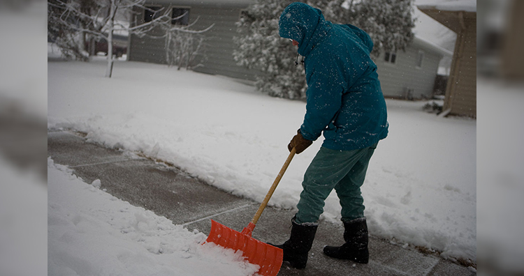 Person shovels snow off his sidewalk